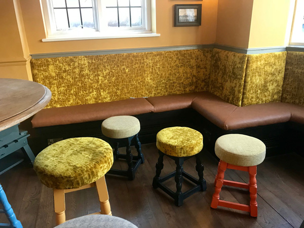 Re-upholstered pub bar seating and backrest with matching stools