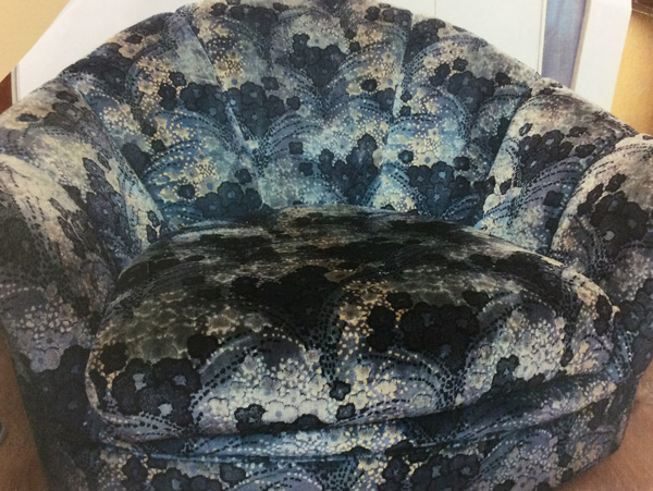 A tub chair covered with a dated and worn fabric