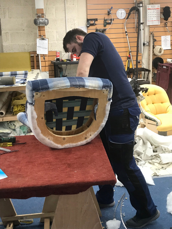 An in-house upholsterer renovating a customer's chair