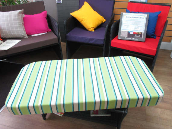 An outdoor cushion in a green striped fabric