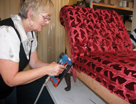 One of our staff members re-upholsters a piece of furniture